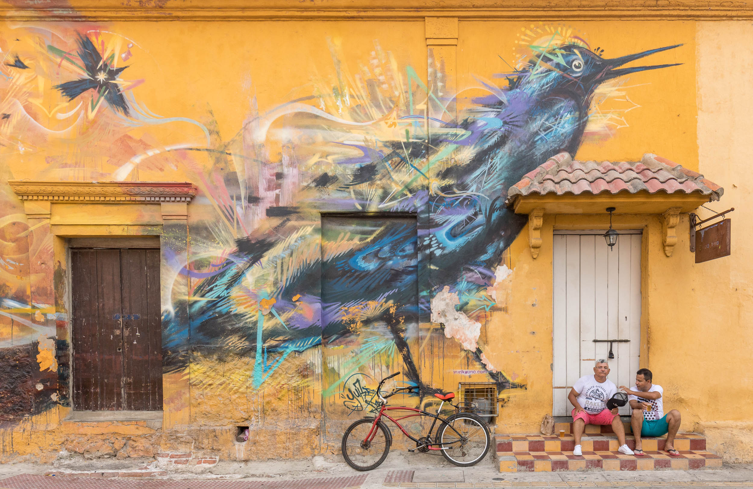 Two men sitting in front of a huge mural of a bird.